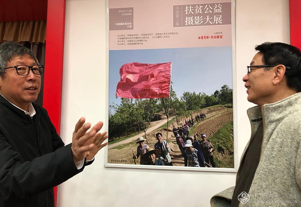 第一书记张国田(左)在招贴前讲述扶贫故事.jpeg