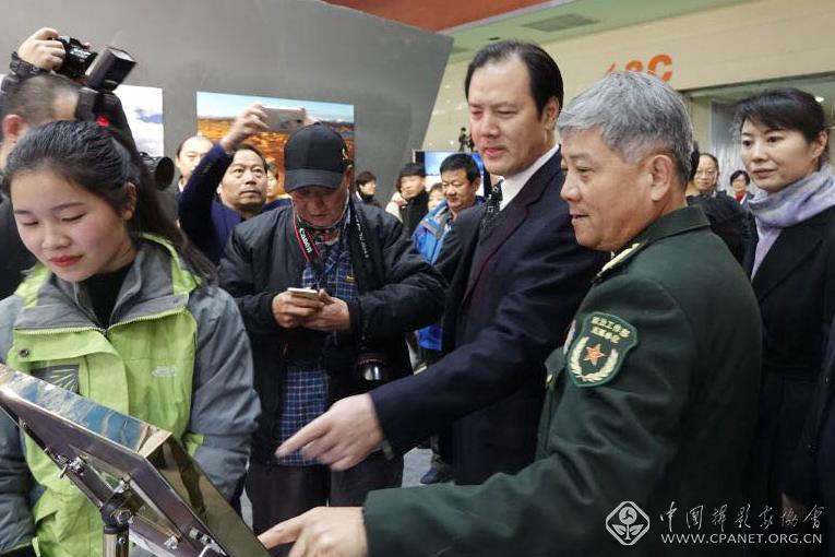 中国文联党组成员、副主席、书记处书记李前光(右三)在展览现场查看最佳拍摄点实例。.jpg