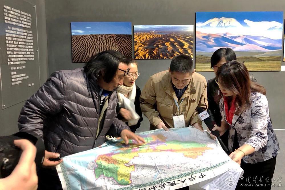 参展摄影师向记者以及观看在线直播的网友介绍阿尔金山在中国地图上所处的位置.jpg